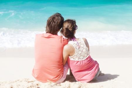 beautiful young couple sitting and having fun on beach Stock Photo