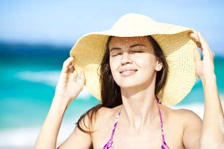 Happy young woman smiling in straw hat with closed eyes on the beach Stock Photo - 17495726