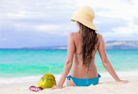 smiling young woman in straw hat with coconut on the beach photo