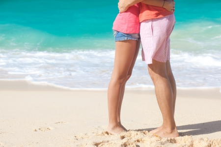 legs of young kissing couple on tropical turquoise boracay beach photo