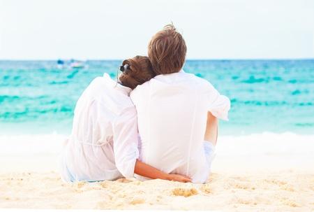 parejas caminando: Vista posterior del joven que se sienta feliz pareja en la playa tropical. concepto luna de miel