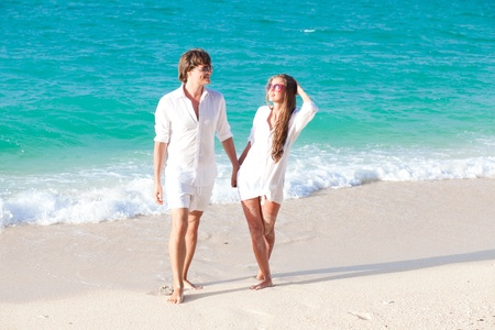 happy young couple walking on the beach photo
