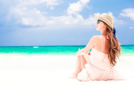 back view of woman in straw hat and dress on tropical beach photo