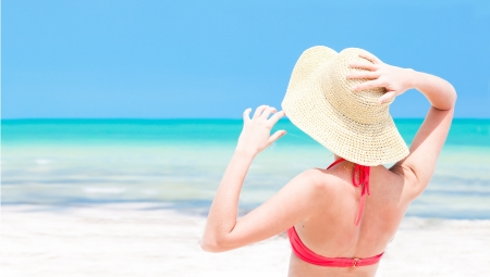 back view of woman in straw hat and bikini on tropical beach photo