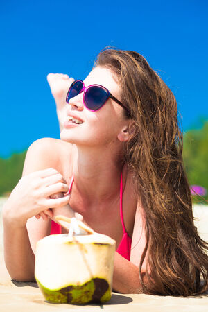 portrait of young woman lying in straw hat in sunglasses with coconut on beach photo