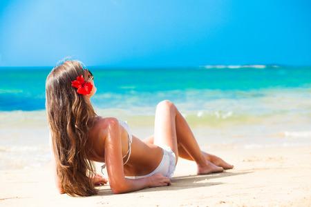 long haired woman with flower in hair in bikini on tropical beach Standard-Bild