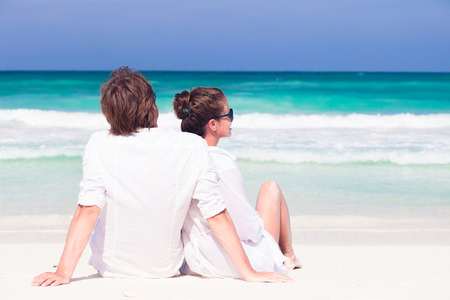 happy young couple in white clothes in sunglasses sitting on beach Stock Photo