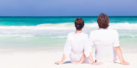back view happy young couple in white clothes in sunglasses sitting on beach Standard-Bild