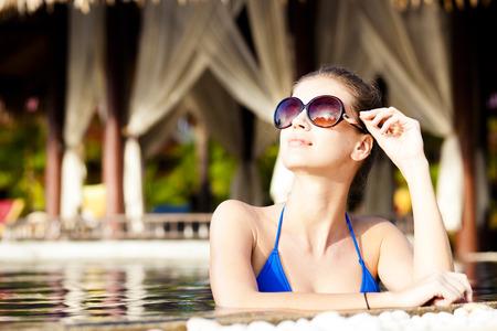 Mooie jonge vrouw in een zonnebril met bloem in het haar lachend in luxe zwembad Stockfoto