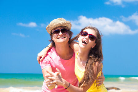 Portrait of happy young couple in sunglasses smiling on beach photo