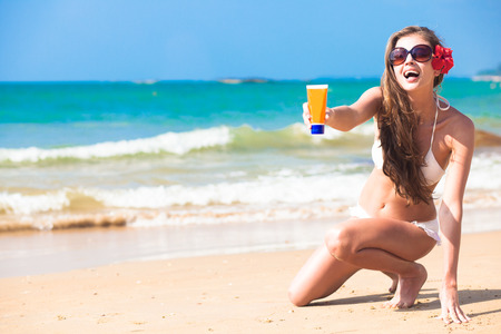 beautiful young woman holding suntan lotion or cream in plastic bottle on tropical beach photo