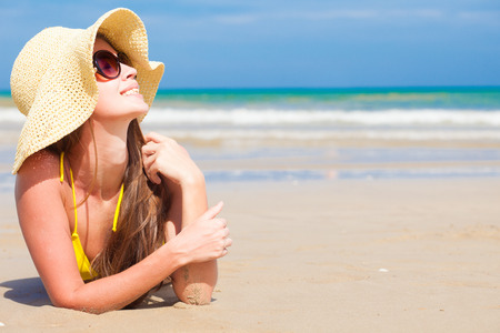 long haired woman in bikini and straw hat on tropical beach Stock Photo