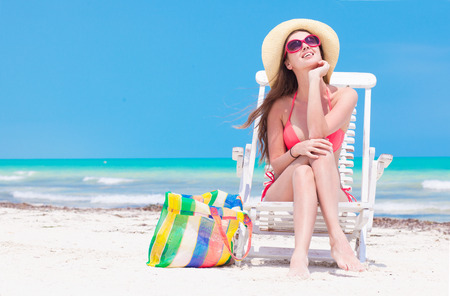 Woman in bikini and straw hat with beach bag sitting on chair on beach. back view