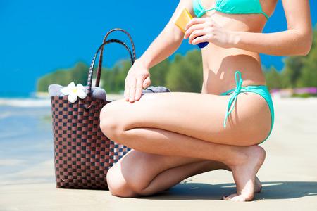 beachbag: Suntan lotion and sunscreen. Woman applying sunblock cream on leg on tropical beach with beachbag