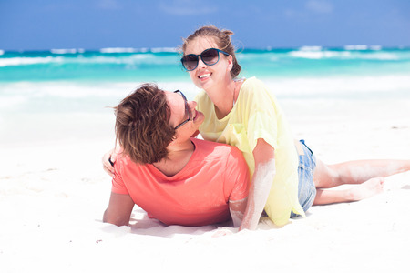Young couple in bright clothes enjoying their time on tropical beach photo
