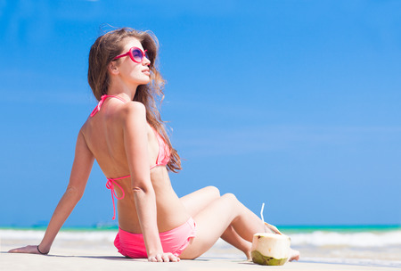 Happy young woman in pink bikini with coconut on the beach photo