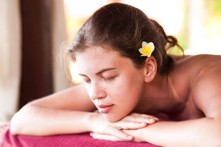 portrait of beautiful young woman with flower in hair lying in spa Stock Photo - 27029609