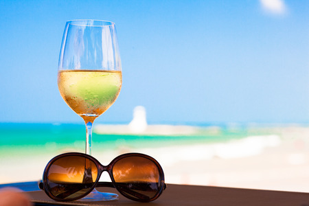 whine: glass of chilled white wine and sunglasses on table near the beach Stock Photo