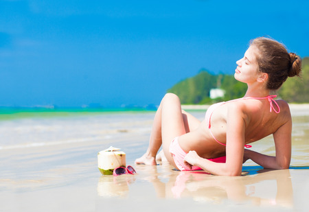 Happy young woman on the beach with coconut cocktail and sunglasses photo