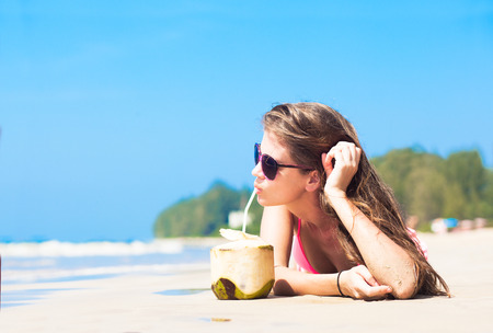 Happy young woman on the beach with coconut cocktail photo