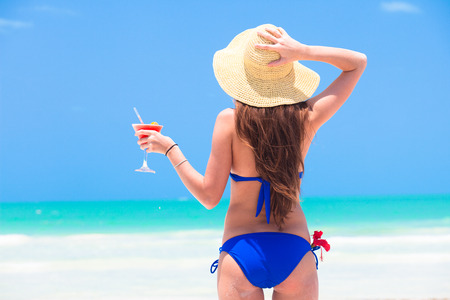 closeup back view young long haired woman in blue bikini with cocktail in hand and straw hat on beach