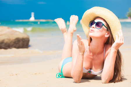 air kiss: portrait of young woman in sunglasses and straw hat blowing an air kiss on beach