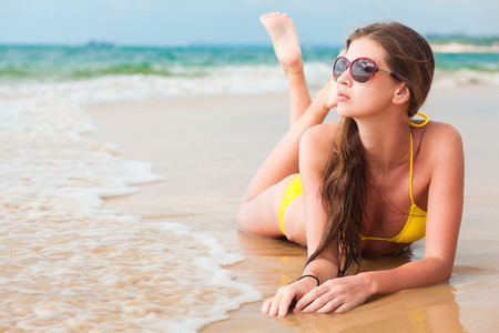 hot girl lying: glamorous long haired young woman in bikini and sunglasses on tropical beach