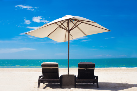 view of the tropical beach with umbrella and two beds