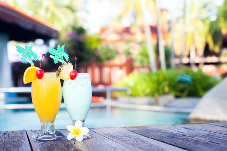 two glasses of cocktails near pool. party