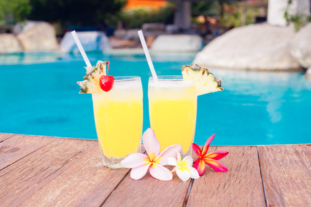 two glasses of bright cocktails and flowers near pool. party photo