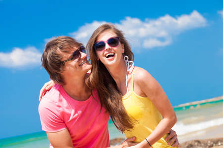 Portrait of happy young couple in sunglasses having fun on tropical beach photo