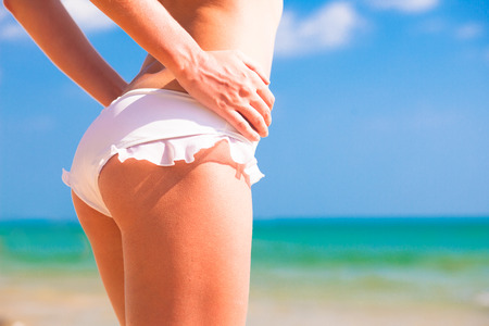 back view of fit young womans bottom in white bikini