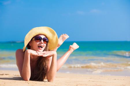 long haired woman in bikini and straw hat on tropical beach Standard-Bild