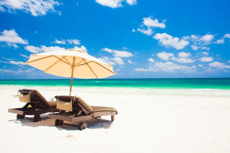 strandstoel: twee strandstoelen en parasol op zand strand. Vakantie