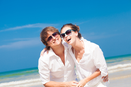 portrait of happy young couple in sunglasses in white clothes smiling outdoors Stock Photo