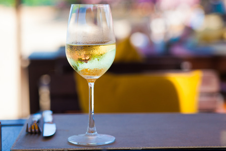 whine: glass of chilled white wine on table near the beach