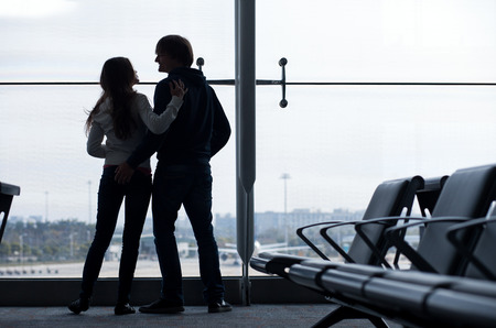 back gate: Silhouette of a couple holding hands and waiting at airport terminal