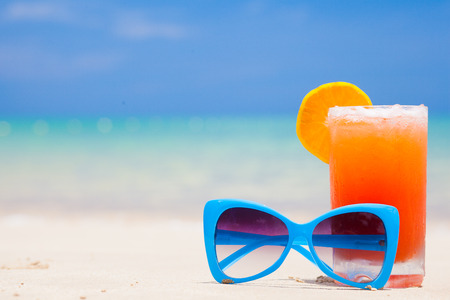 fresh fruit cocktail with blue sunglasses on tropical beach