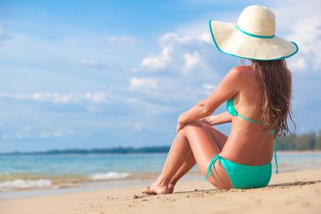 long haired girl in bikini and straw hat on tropical beach