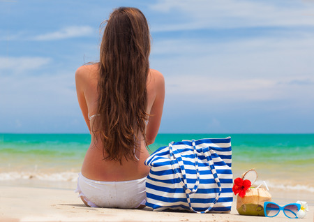 back view of a woman in bikini with beach bag and coconut cocktail photo