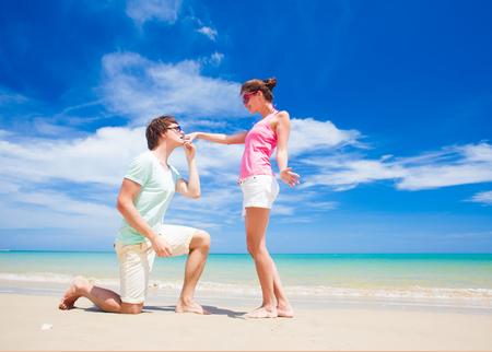 Freund, der auf einem Knie küssen Mädchen Hand am tropischen Strand