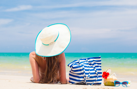 back view of a woman in bikini and straw hat with beach bag and coconut cocktail