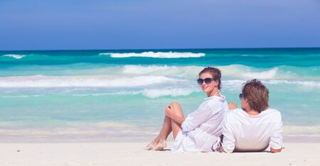 portrait of happy young couple in sunglasses in white clothes sitting on tropical beach