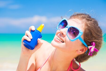 sun screen: Young woman in sunglasses holding sun cream in hand Stock Photo