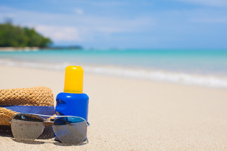 holidays vacancy: Sunscreen, hat and sunglasses on tropical beach Stock Photo