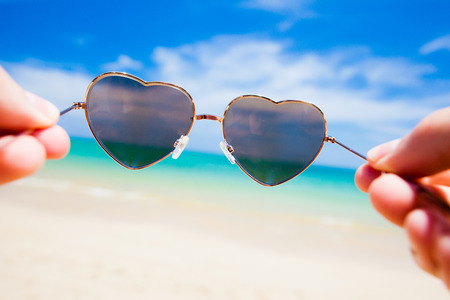close up of heart shaped sunglasses. sunny beach in thailand photo