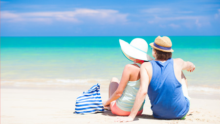 back view of couple sitting at tropical beach photo