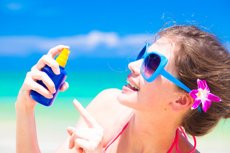 Young woman in sunglasses holding sun cream in hand Stock Photo