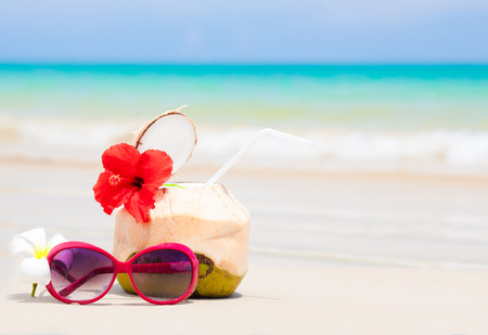 picture of fresh cocnut cocktail and red sunglasses on tropical beach Standard-Bild