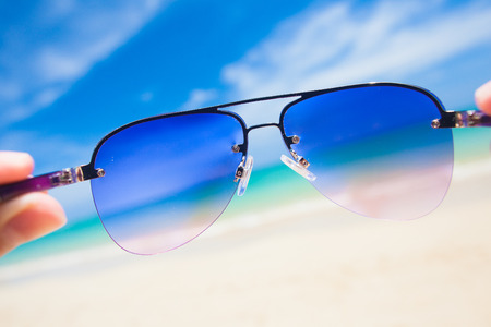 close up of colorful sunglasses  tropical Thailand beach  travel concept photo